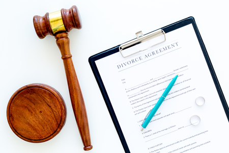 Divorce court case. Divorce agreement near wedding rings and judge gavel on white background top view.