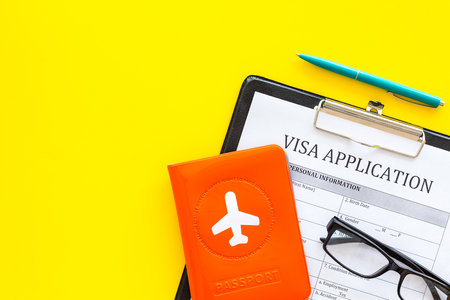 Fill visa application form. Form near glasses, pen, passport cover with airplane sign on yellow background top view Stock Photo
