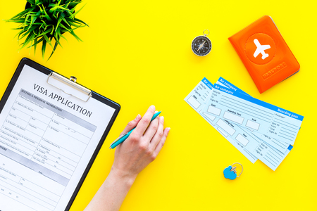 Hand fills visa application form. Form near glasses, pen, passport cover with airplane sign and airplane tickets on yellow background top view.