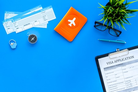 Documents for travel abroad. Visa application form, pen, passport cover with airplane silhouette on blue background top view. Stock Photo