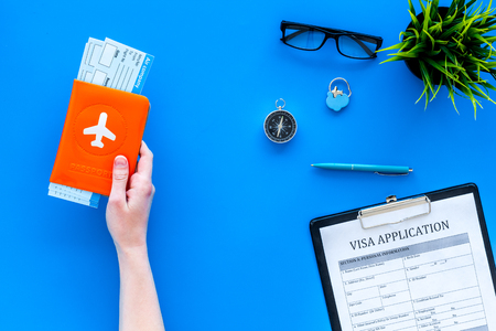 Planning vacation. Visa processing. Hand hold airplane tickets in passport cover with airplane silhouette near visa application form, compas on blue background top view.