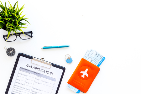 Planning vacation. Visa processing. Airplane tickets near passport cover with airplane silhouette, visa application form, compass on white background top view. Stock Photo