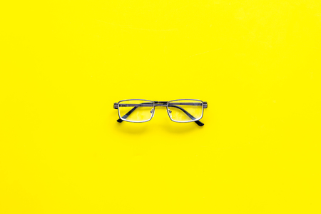 One glasses with transparent lenses on yellow background top view.
