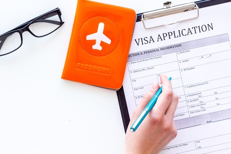 Hand fills visa application form. Form near glasses, pen, passport cover with airplane sign on white background top view. Stock Photo