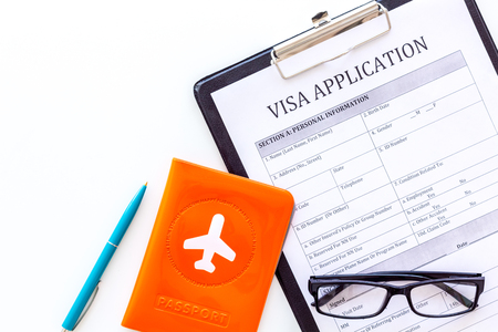 Fill visa application form. Form near glasses, pen, passport cover with airplane sign on white background top view. Stock Photo