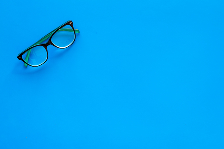 One glasses with transparent lenses on blue background top view.