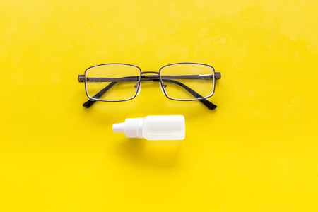 Eye drops in small bottle near glasses on yellow background top view. Stock Photo - 104081095