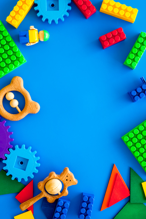 Colored construction toys for children frame on blue background top view.