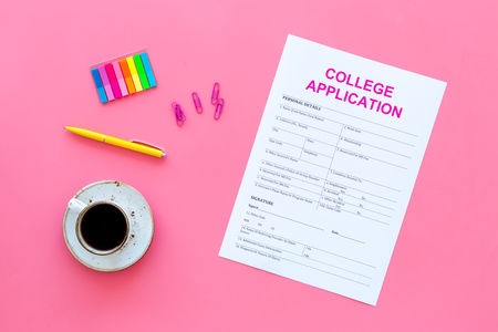 Higher education. College application form ready to fill near coffee cup and stationery on pink background top view.