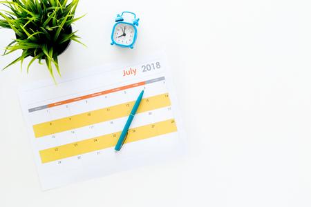 Planning concept. Doelen en taken voor de maand. Lege maandkalender dichtbij wekker op witte hoogste mening als achtergrond. Stockfoto