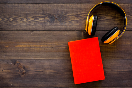 Books online concept, audiobooks. Spend leasure time reading and listening music. Headphones near hardback book with empty cover on dark wooden background top view copy space