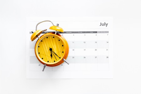 Deadline concept. Alarm clock on calendar on white background top view copy space Stock Photo
