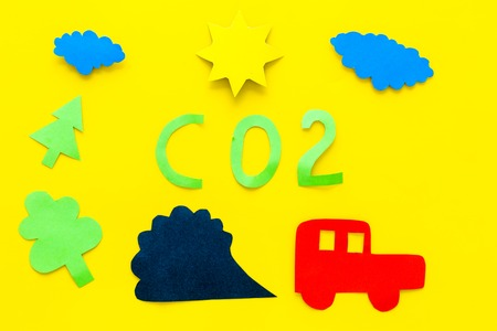 Cars emitting carbon dioxide. Pollution concept. harm the environment. Car and smoke cutout on yellow background top view