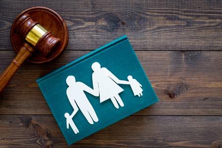 Prawo rodzinne, pojęcie prawa rodzinnego. Pojęcie opieki nad dzieckiem. Rodzina z dziećmi wyłącznik w pobliżu dworu młotek na ciemnym drewnianym tle widok z góry kopia przestrzeń Zdjęcie Seryjne