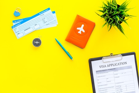 Prepare to trip. Do visa. Airplane tickets near passport cover with airplane silhouette, visa application form, compas on yellow background top view copy space Фото со стока