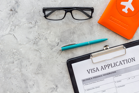 Visa prosessing. Registration of visas. Visa application form, pen, passport cover with airplane silhouette on grey background top view copy space