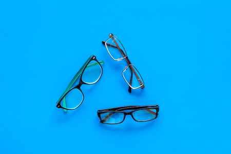Glasses concept. Set of glasses with different eyeglass frame and transparent lenses on blue background top view copy space Stock Photo - 104215159
