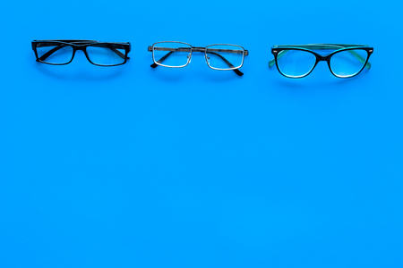 Glasses concept. Set of glasses with different eyeglass frame and transparent lenses on blue background top view space for text pattern