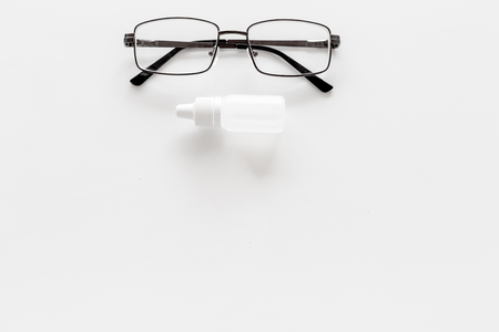 Eye drops in small bottle near glasses on white background top view copy space Reklamní fotografie