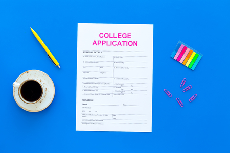 Higher education. College application form ready to fill near coffee cup and stationery on blue background top view Imagens