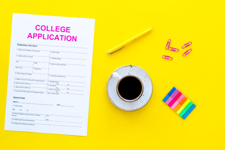 Higher education. College application form ready to fill near coffee cup and stationery on yellow background top view