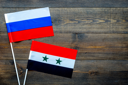 Russia-Syria relations. Country cooperation. Russian and Syrian flags on dark wooden background top view copy space