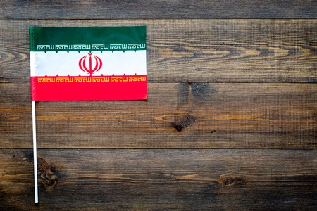 Iranian flag concept. small flag on dark wooden background top view copy space 스톡 콘텐츠 - 104215311