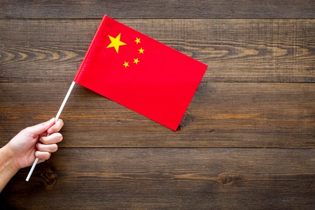 Chinese flag concept. Hand hold small flag on dark wooden background top view copy space Stok Fotoğraf