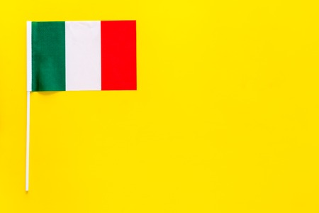 Italian flag concept. small flag on yellow background top view copy space 스톡 콘텐츠