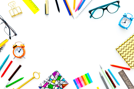Education background, frame. School, student, office supplies. Stationery, glasses, alarm clock, notebook on white background top view copy space Stock Photo
