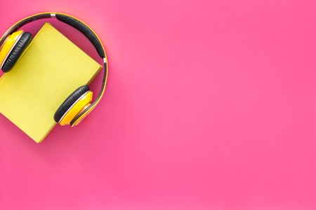Audiobooks concept. Headphones put over hardback book with empty cover on pink background top view copy space Stock Photo