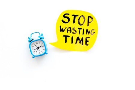 Stop wasting time hand lettering near alarm clock on white background top view copy space. Business concept, motivation