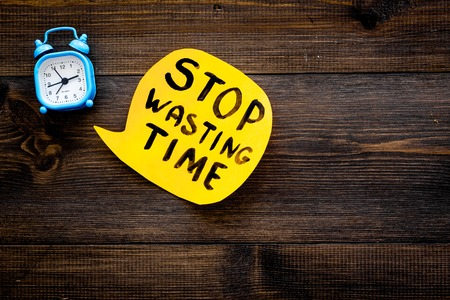 Stop wasting time hand lettering in cloud near alarm clock on dark wooden background top view copy space. Business concept, motivation