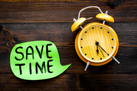 Time-management. Save time hand lettering in cloud near alarm clock on dark wooden background top view copy space