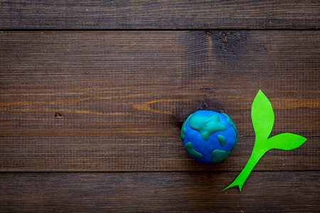 Planet, ecology. Plasticine symbol of planet Earth globe and plant cut out on dark wooden background top view copy space Stockfoto