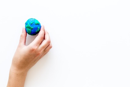 Earth. Hand hold Plasticine symbol of planet Earth globe on white background top view copy space Banco de Imagens