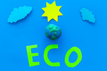 Eco icon cutout near Plasticine symbol of planet Earth, sun, clouds on blue background top view copy space