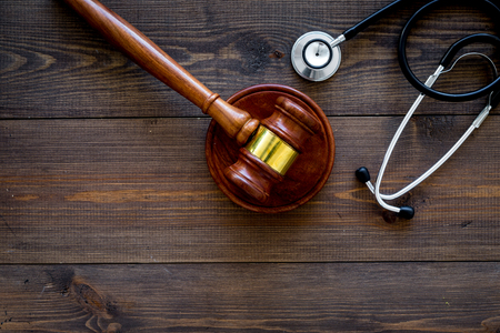 Medical law, health law concept. Gavel and stethoscope on dark wooden background top view copy space