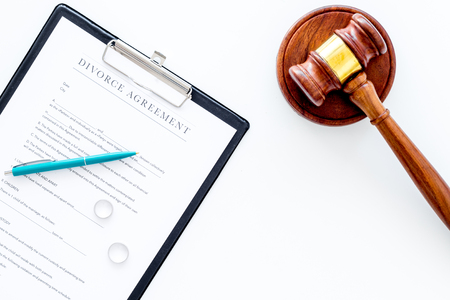 Divorce court case. Divorce agreement near wedding rings and judge gavel on white background top view copy space