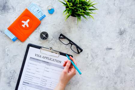 Hand fills visa application form. Form near glasses, pen, passport cover with airplane sign and airplane tickets on grey background top view copy space