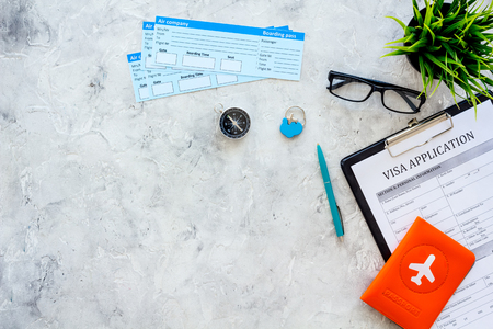 Documents for travel abroad. Visa application form, pen, passport cover with airplane silhouette, airplane tickets on grey background top view copy space