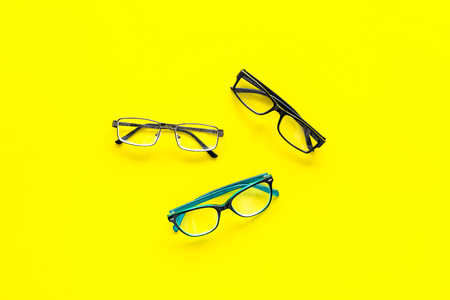 Glasses concept. Set of glasses with different eyeglass frame and transparent lenses on yellow background top view copy space Stock Photo