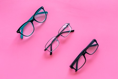 Glasses concept. Set of glasses with different eyeglass frame and transparent lenses on pink background top view copy space