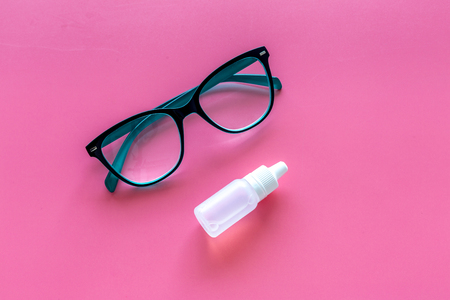 Eye drops in small bottle near glasses on pink background top view copy space