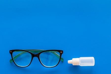 Eye drops in small bottle near glasses on blue background top view copy space Reklamní fotografie - 104261511