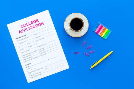 Higher education. College application form ready to fill near coffee cup and stationery on blue background top view 스톡 콘텐츠
