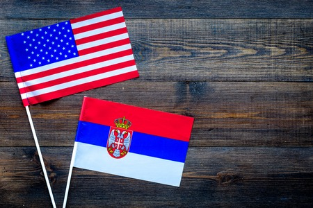 USA-Serbia relations. Country cooperation. American and Serbian flags on dark wooden background top view copy space