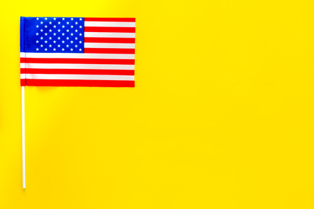 American flag concept. Small flag on yellow background top view copy space