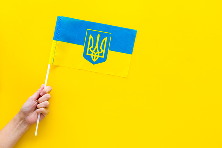 Ukrainian flag concept. Hand hold small flag on yellow top view copy space