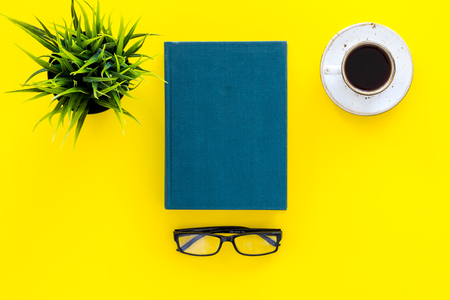 Book with empty cover near glasses, coffe, plant on yellow desk top view space for text. Spend time reading. Self-development concept. Stock Photo